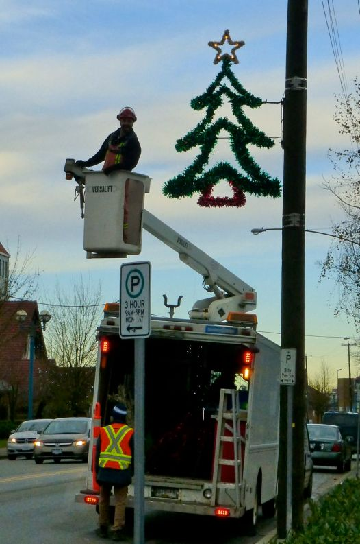 Workmen putting up Christmas lights